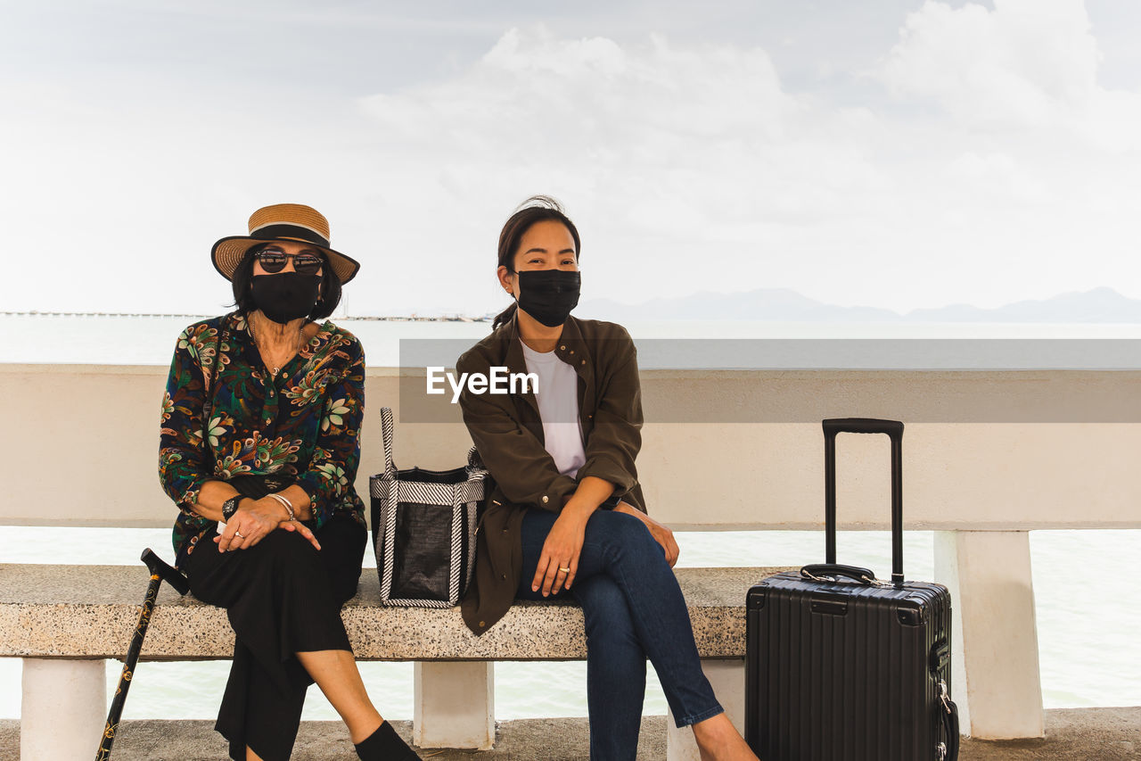 Full length of femals wearing protective mask and sunglasses sitting against sky