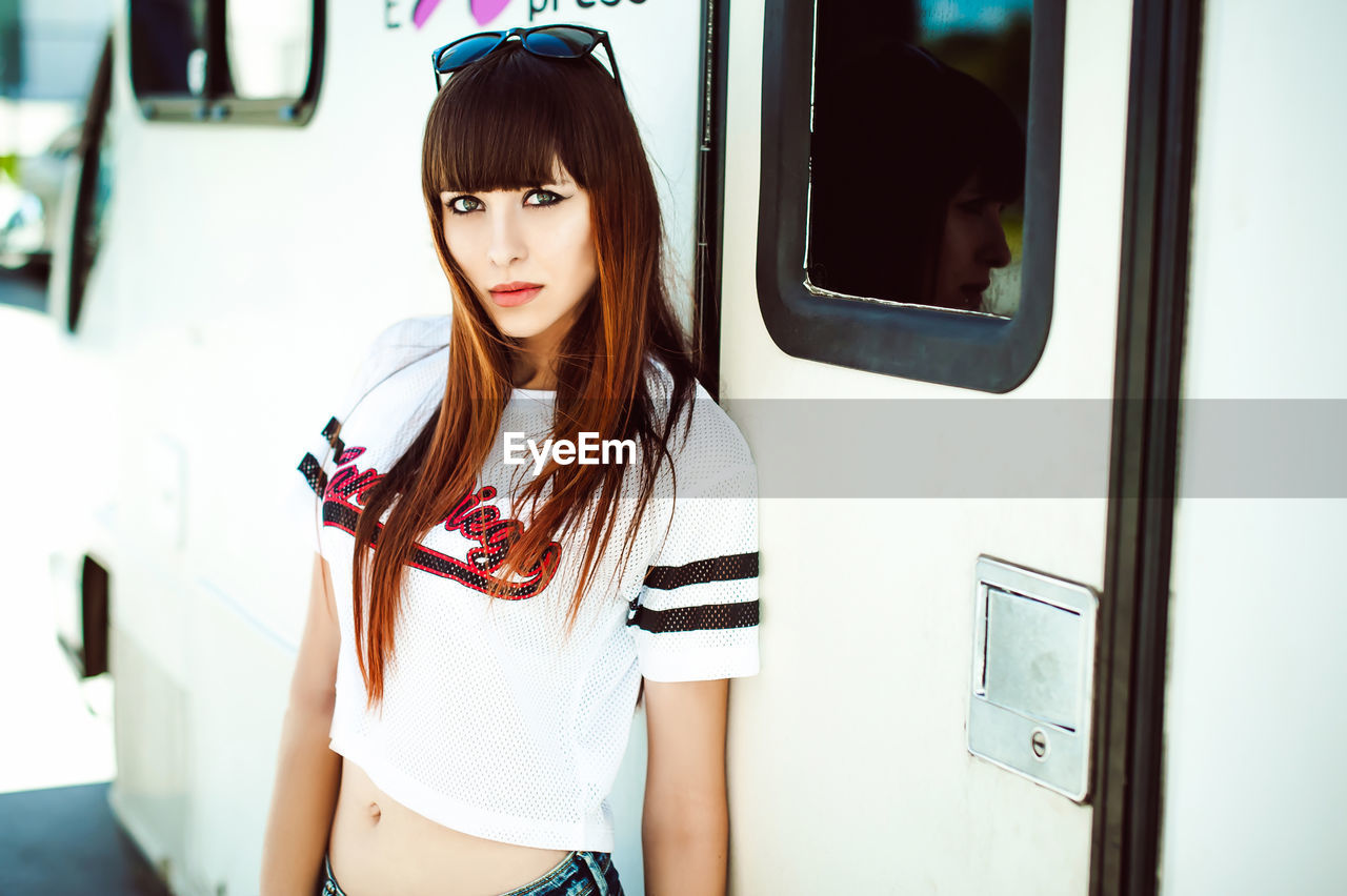 Portrait of young woman standing by camper trailer