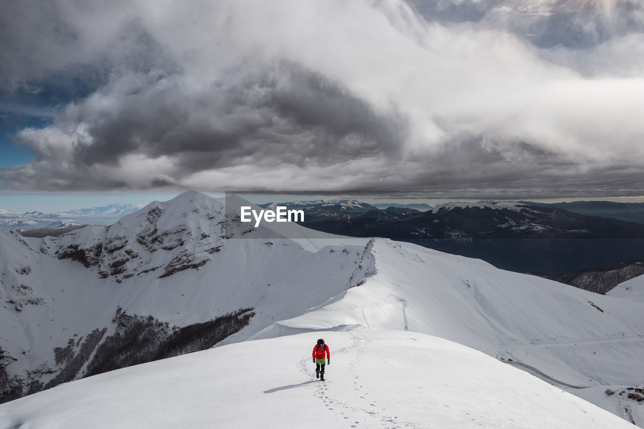 mountain, snow, cloud - sky, winter, cold temperature, beauty in nature, scenics - nature, sky, mountain range, leisure activity, one person, adventure, sport, snowcapped mountain, lifestyles, real people, winter sport, non-urban scene, white color, outdoors, ski-wear