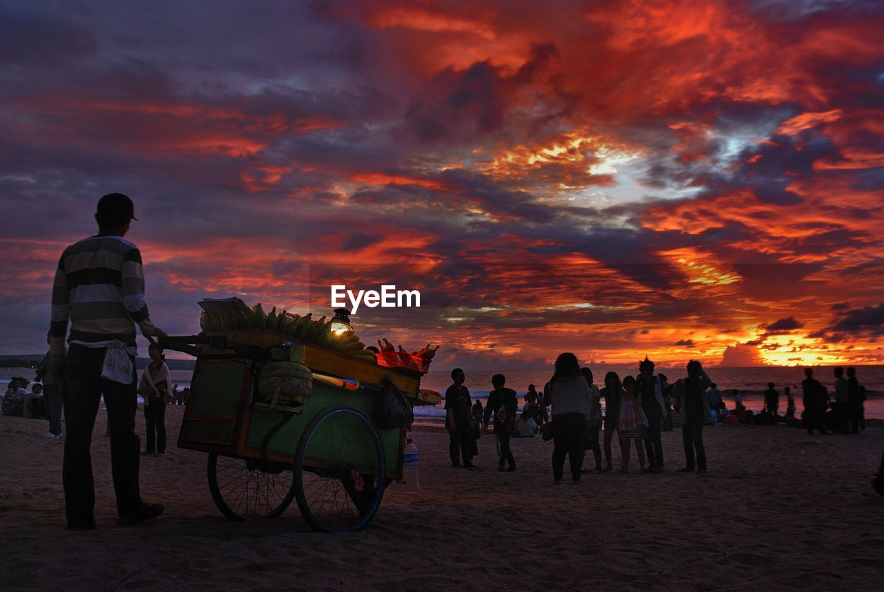 Full Length Rear View Of Vendor Selling Sweetcorns At Beach Against Orange Sky