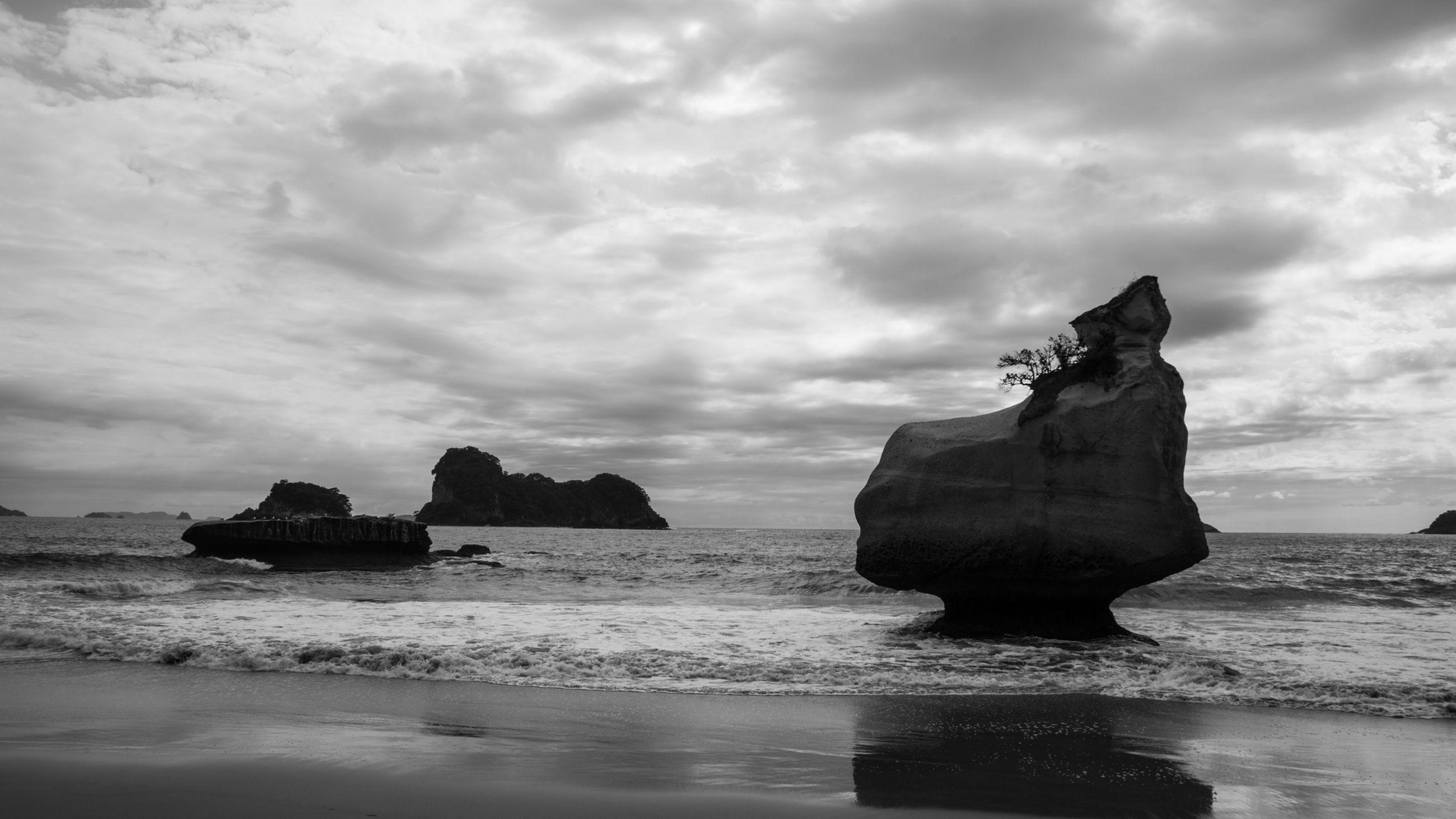 Rocks on sea against cloudy sky