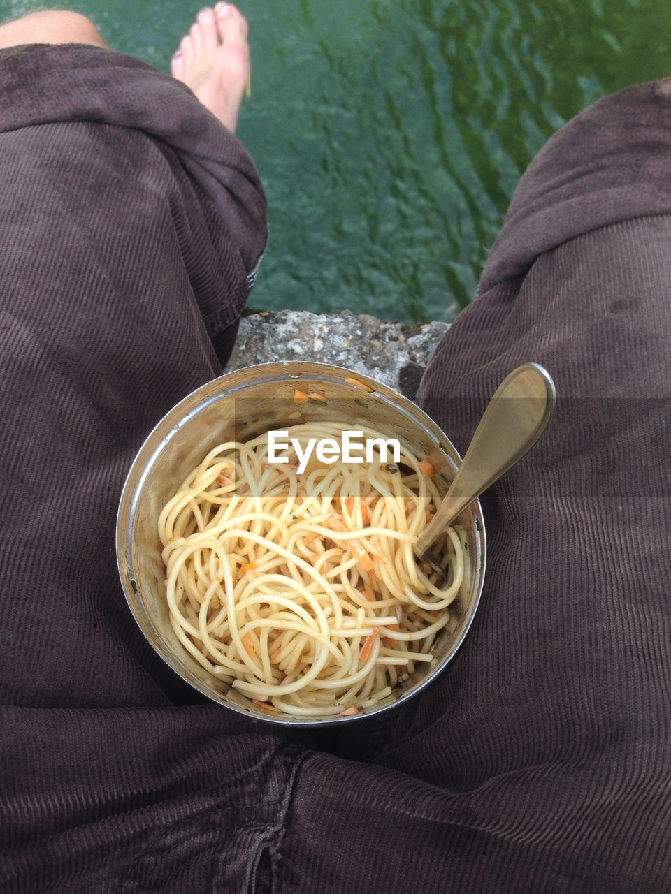 Low Section Of Person Sitting With Noodles In Bowl At Pier
