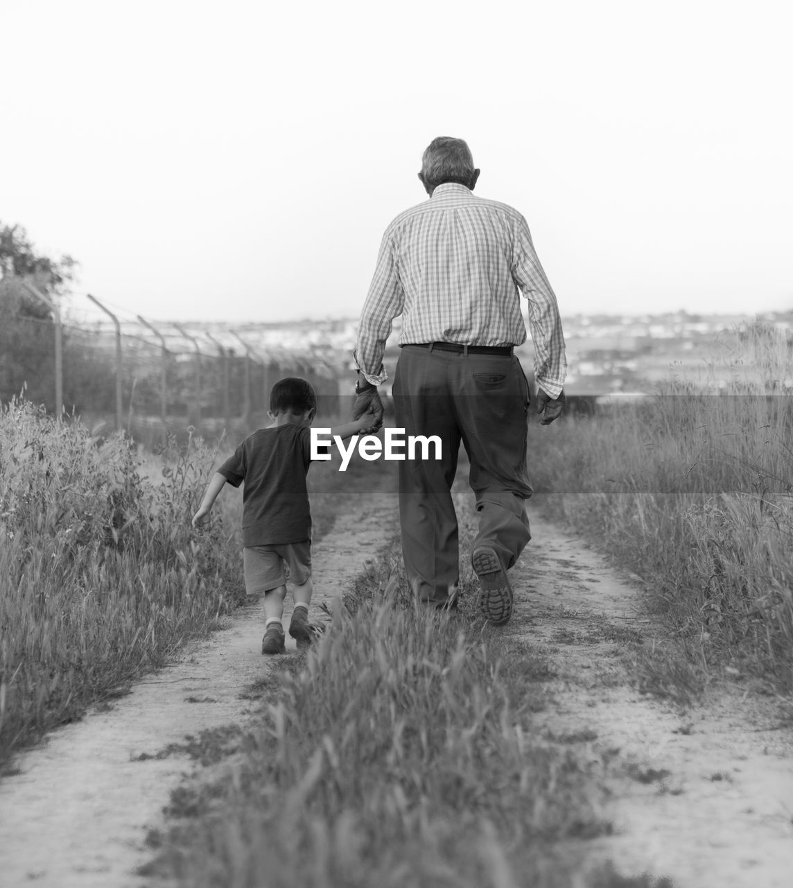Rear view of father and son walking on field