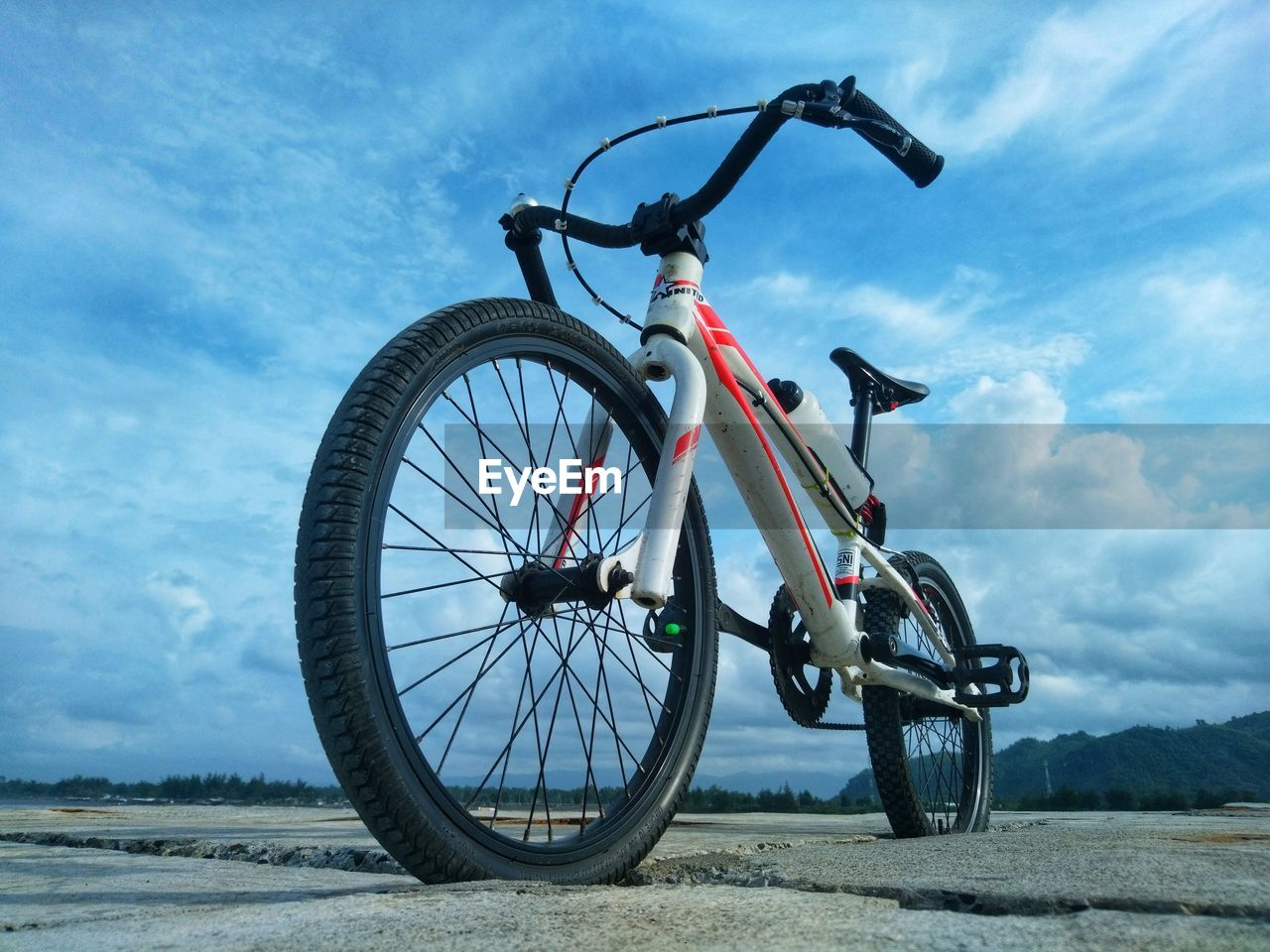 LOW ANGLE VIEW OF BICYCLE WHEEL ON FIELD