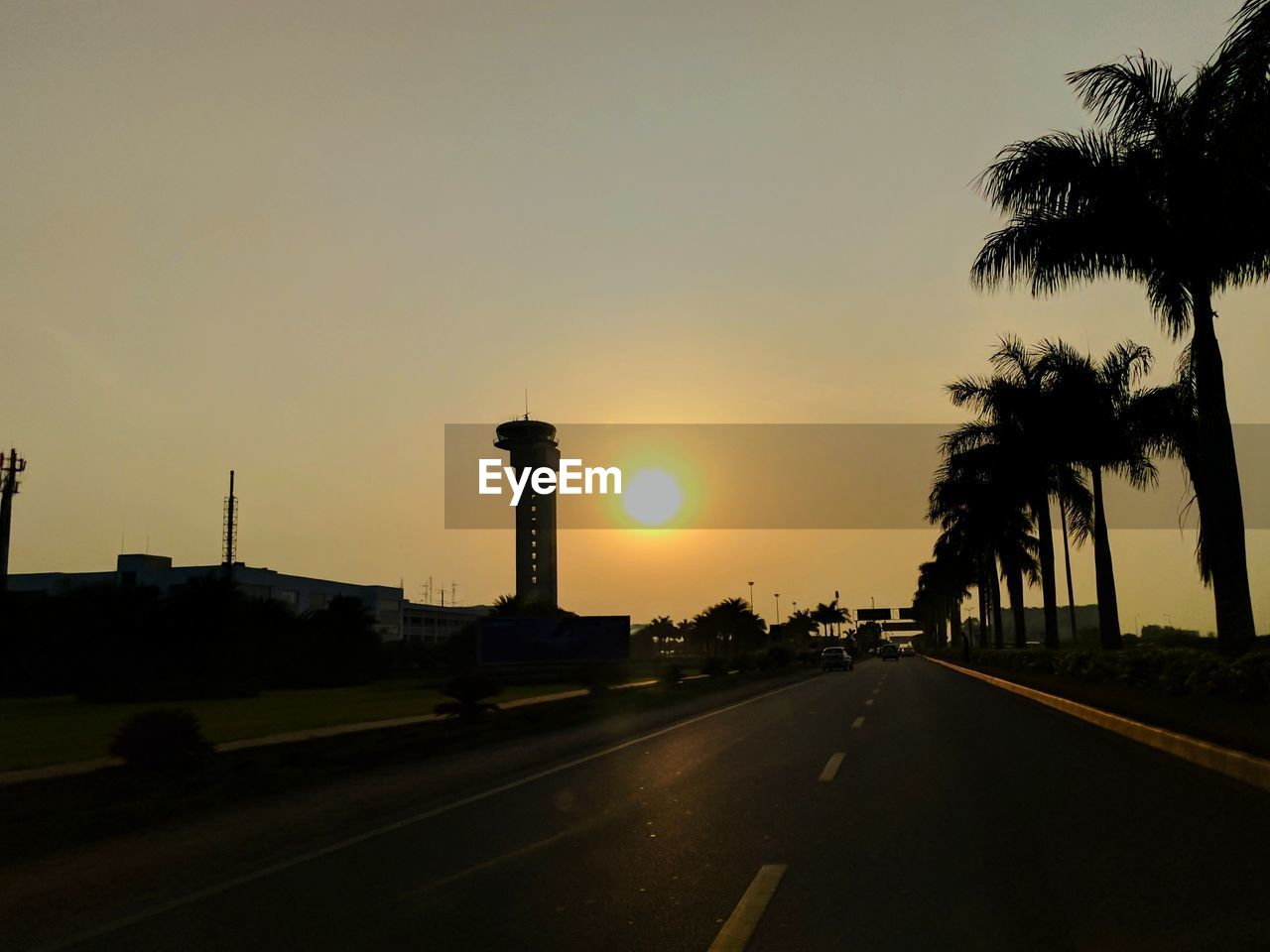 sunset, road, silhouette, tree, no people, sun, transportation, sky, the way forward, palm tree, built structure, outdoors, architecture, nature, city, day