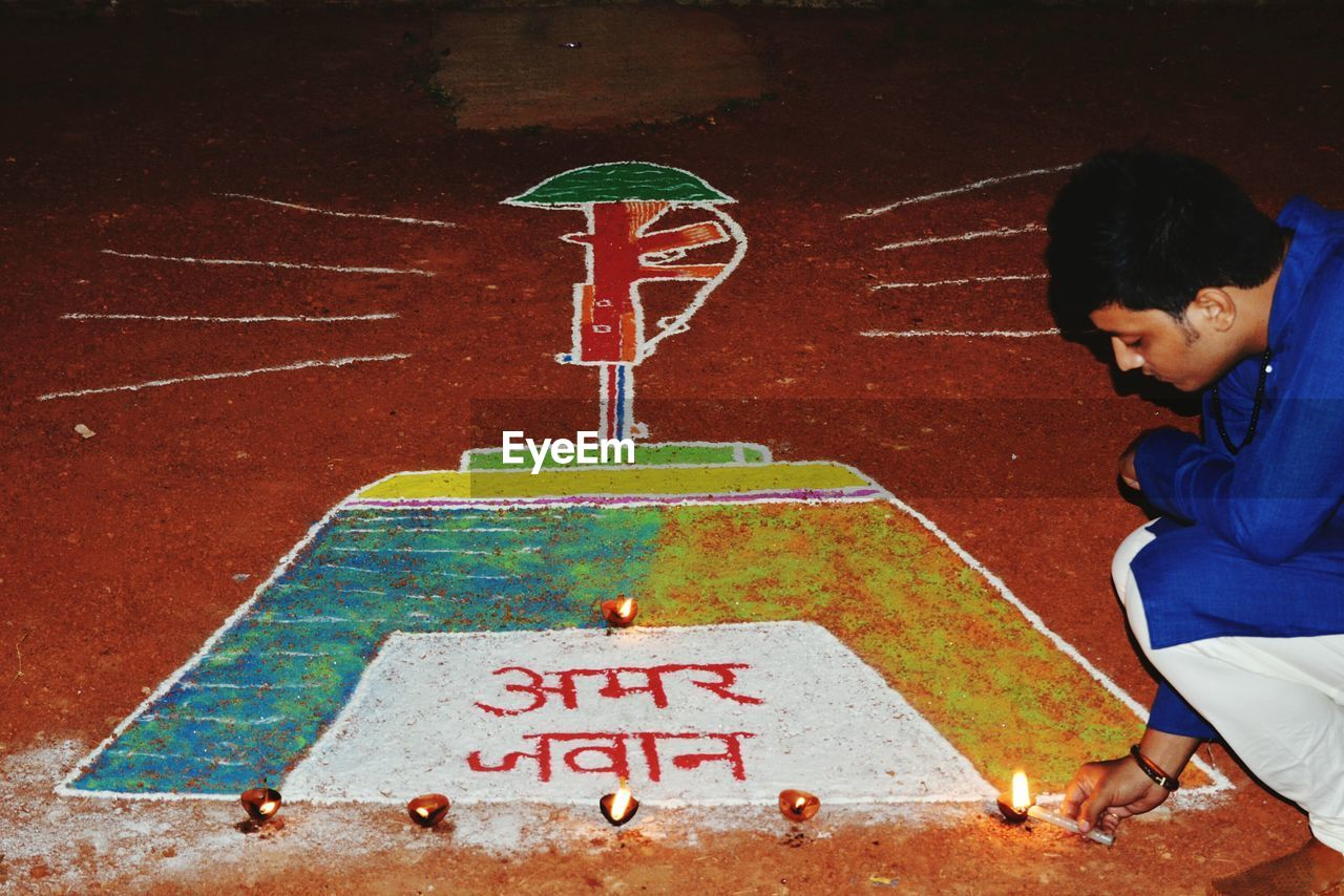 Man Crouching While Igniting Diya From Candle By Rangoli