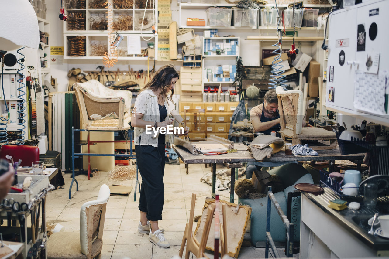 occupation, real people, women, adult, workshop, one person, fashion, small business, business, standing, indoors, creativity, three quarter length, art and craft, casual clothing, day, full length, working, textile, design professional, consumerism