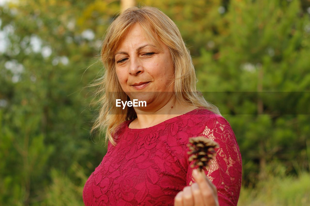 Mature woman showing pine cone while standing against trees