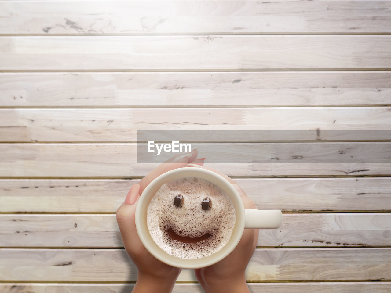 wood - material, one person, coffee, drink, food and drink, refreshment, coffee - drink, directly above, cup, coffee cup, mug, human body part, real people, holding, human hand, frothy drink, indoors, unrecognizable person, lifestyles, hand, wood
