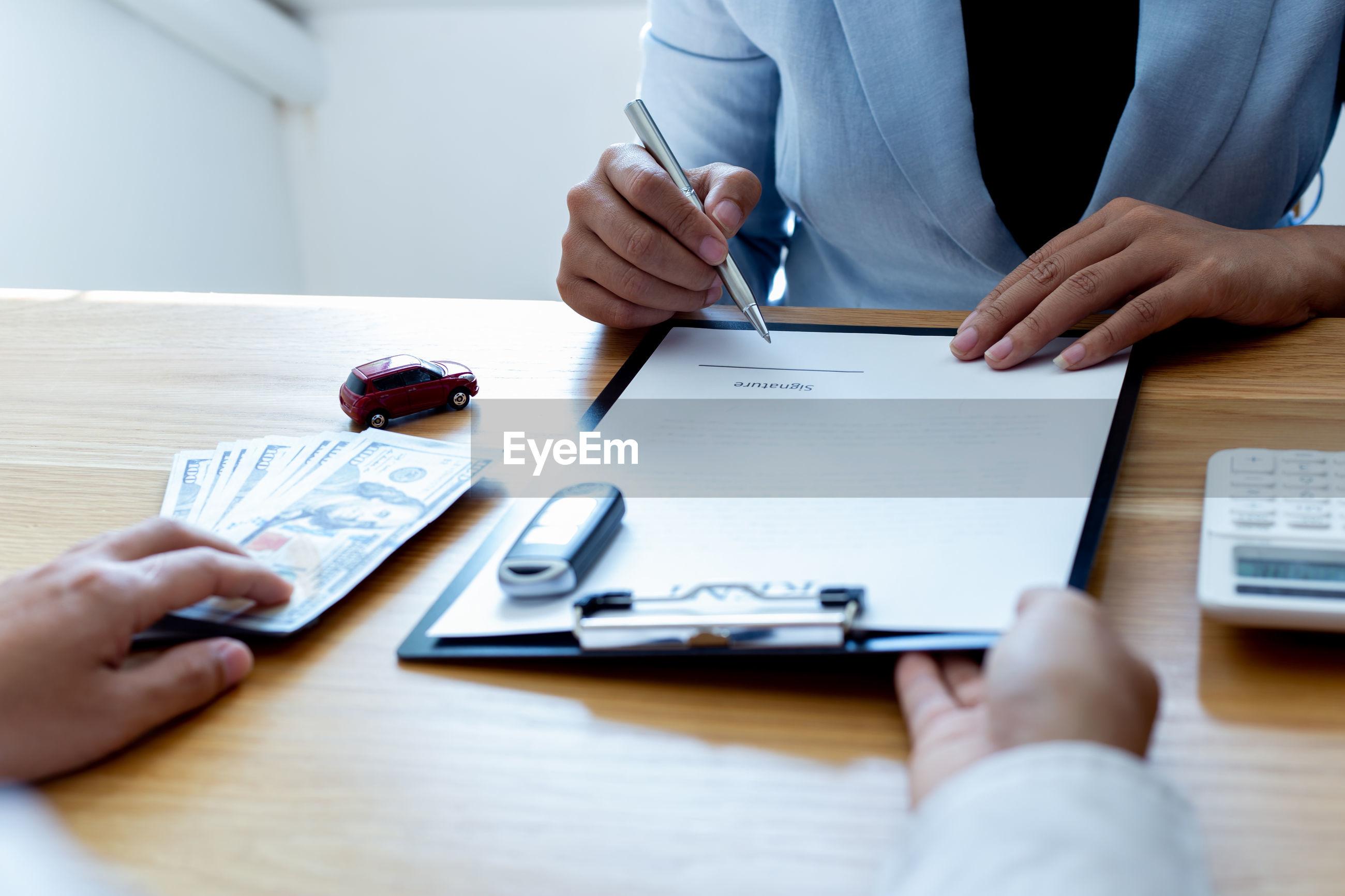 Car salesman giving contract to customer