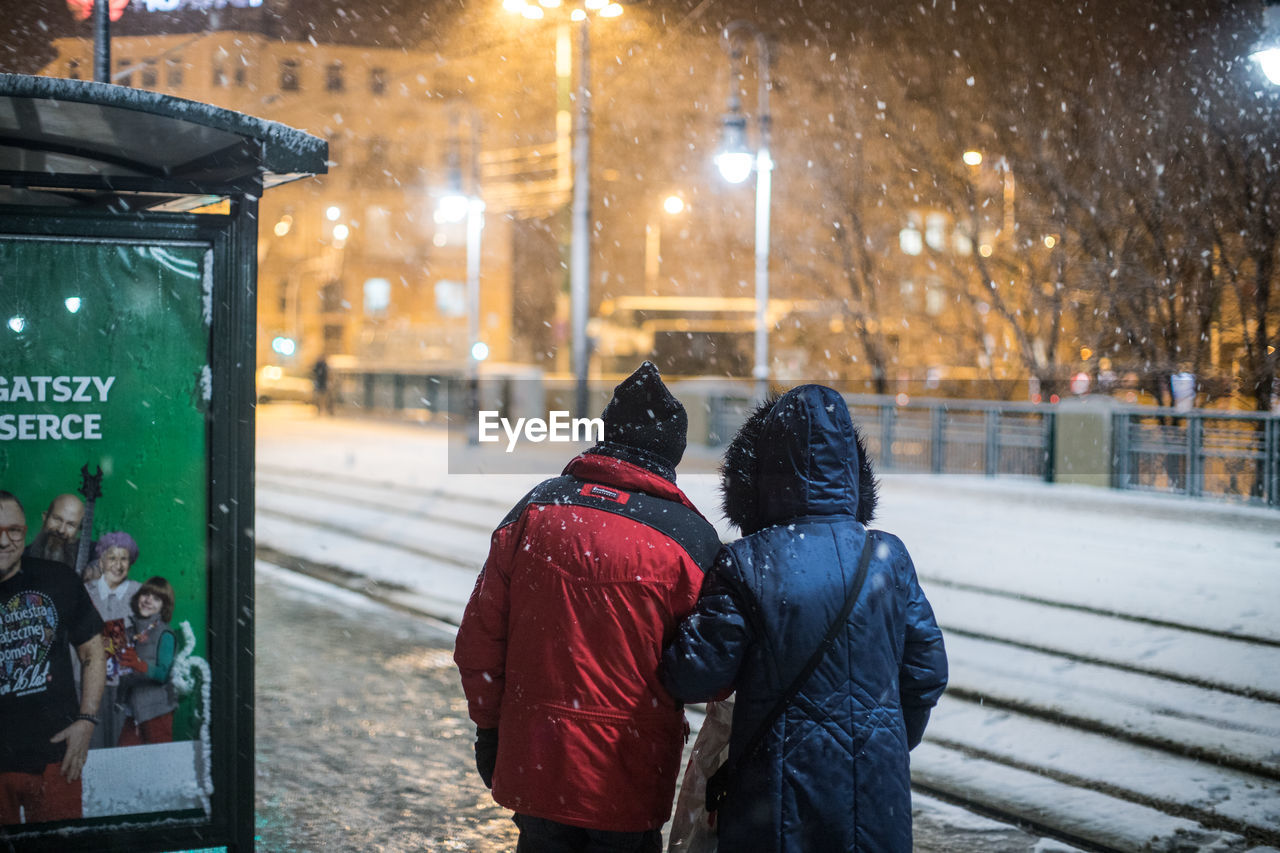 winter, cold temperature, snow, weather, warm clothing, rear view, real people, knit hat, snowing, women, leisure activity, two people, night, focus on foreground, men, outdoors, lifestyles, togetherness, nature, ice rink, adult, people