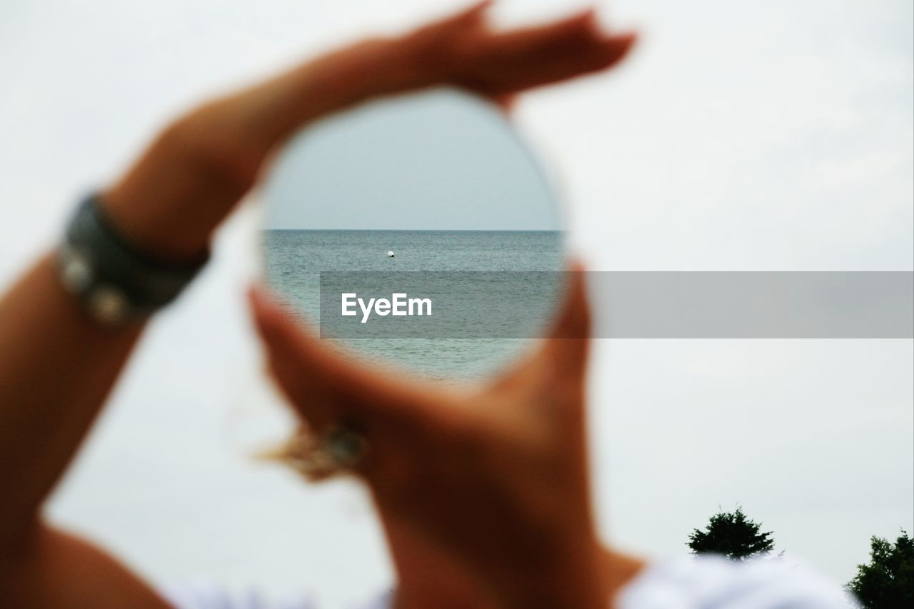 human hand, real people, one person, close-up, human body part, leisure activity, sky, holding, lifestyles, outdoors, women, day, water, nature, people
