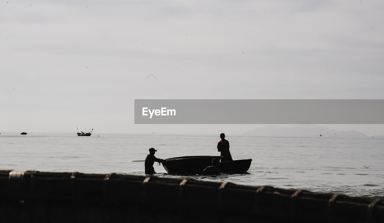 SILHOUETTE MEN SITTING ON BOAT AGAINST SEA