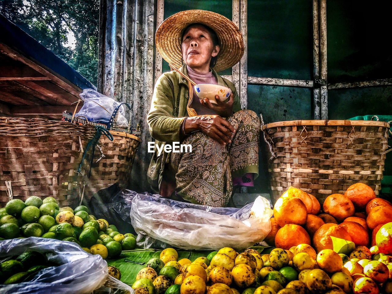 healthy eating, real people, food, market, vegetable, one person, hat, market stall, food and drink, front view, clothing, retail, day, freshness, business, container, fruit, portrait, women, outdoors