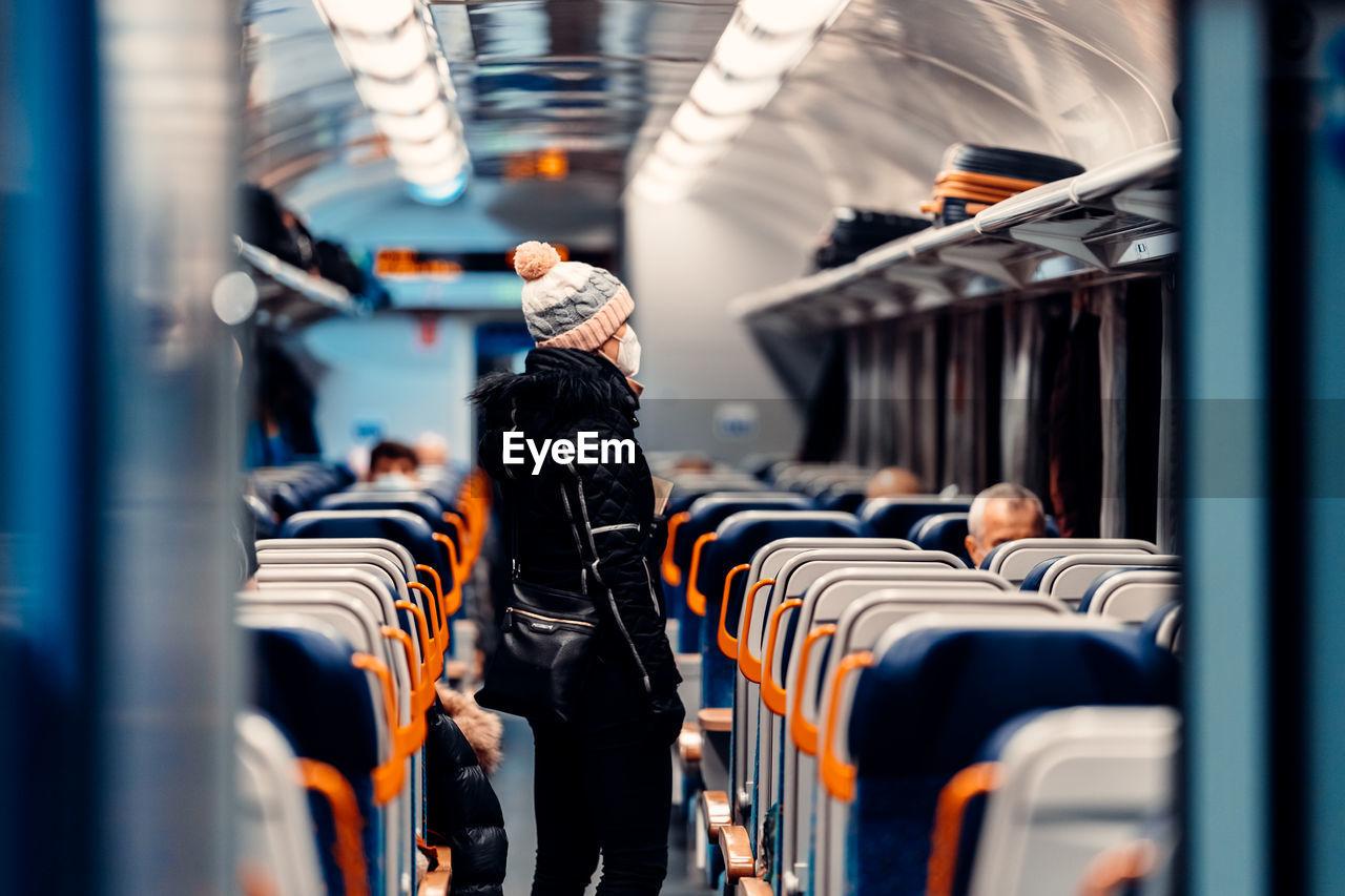 Woman wearing knit hat standing in train