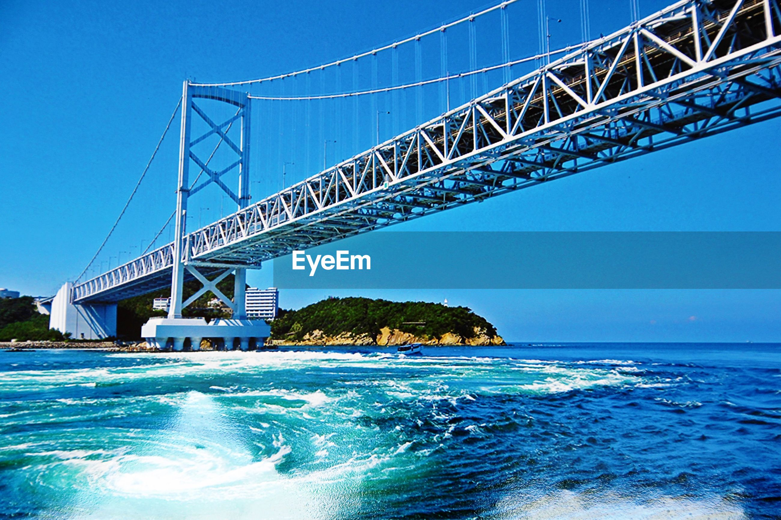 LOW ANGLE VIEW OF BRIDGE OVER CALM BLUE SEA