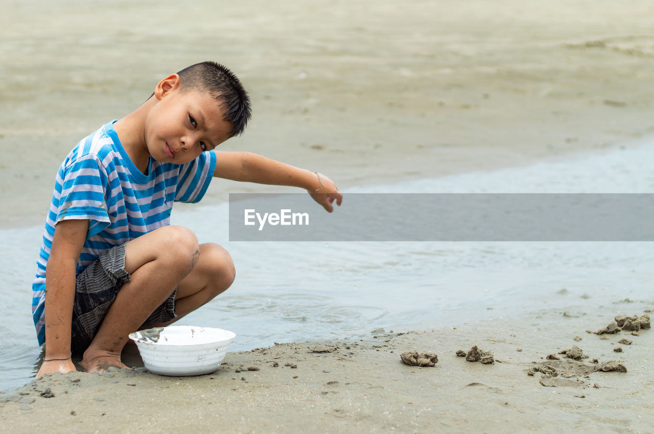 Portrait of boy crouching on shore at beach