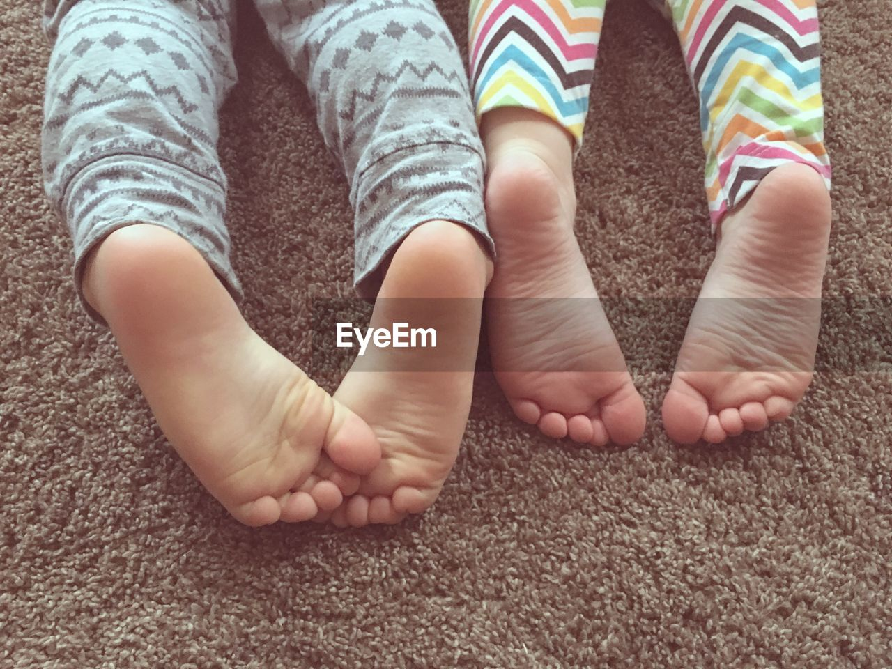Low Section Of Kids Lying On Rug At Home