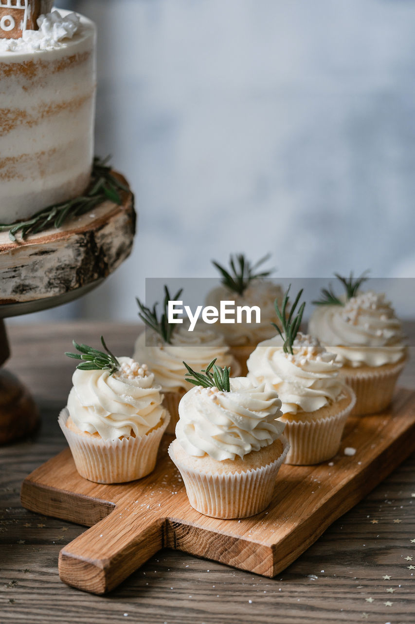 CLOSE-UP OF CUPCAKES ON TABLE AGAINST WALL