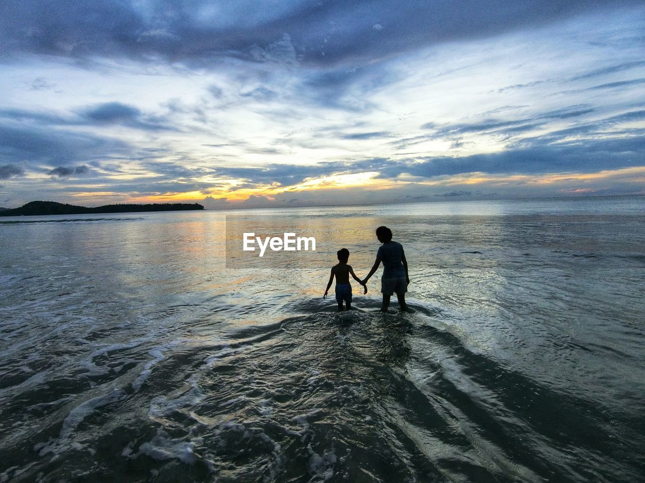 Mother and son wading in sea against sky during sunset