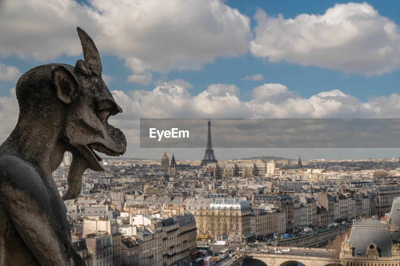 Gargoyle statue in city against sky