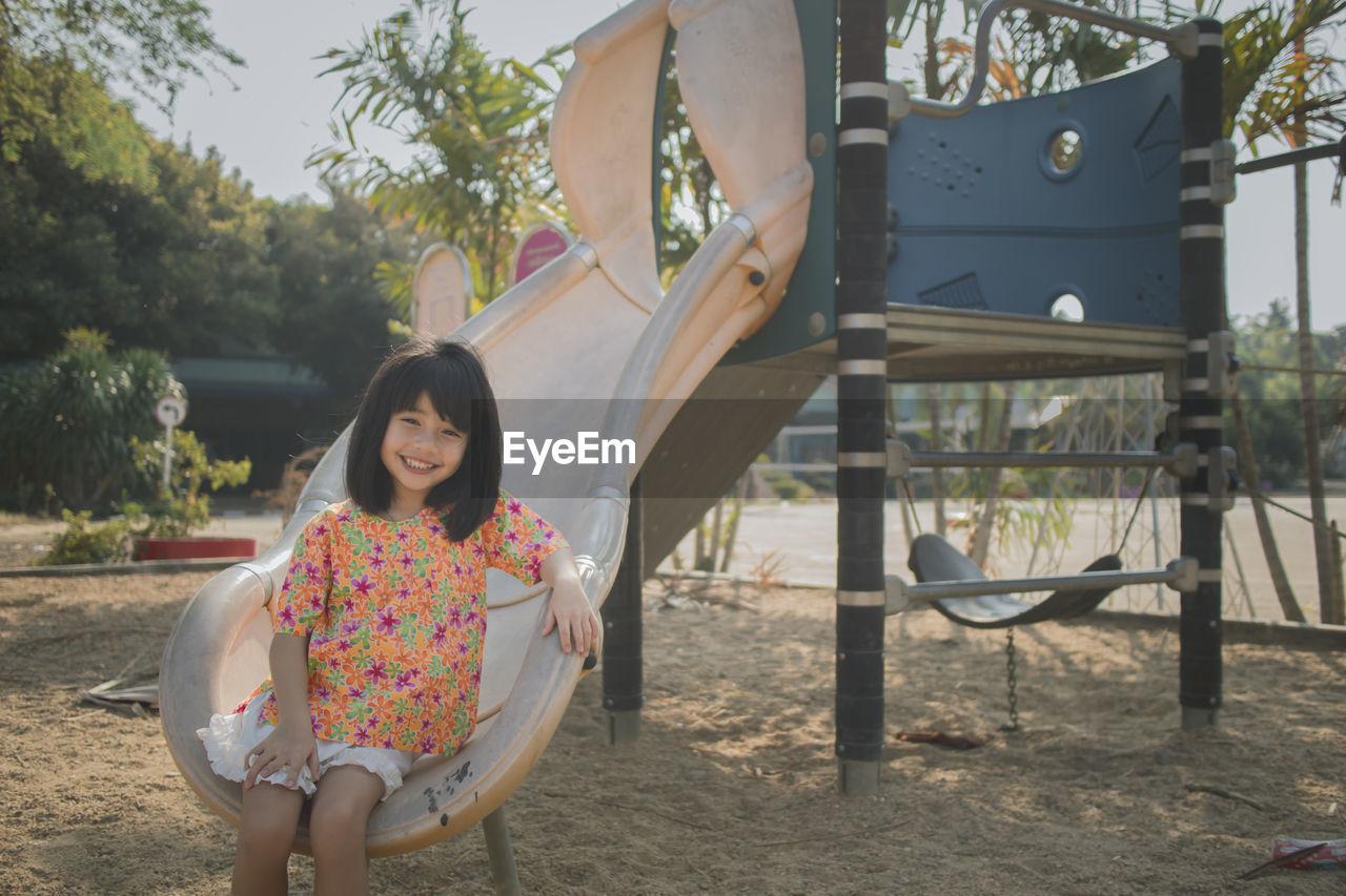 Portrait of smiling cute girl sitting on slide in park