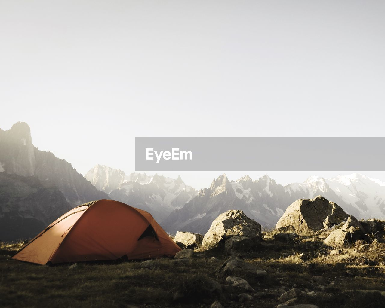 Tent On Field By Rocky Mountains Against Clear Sky