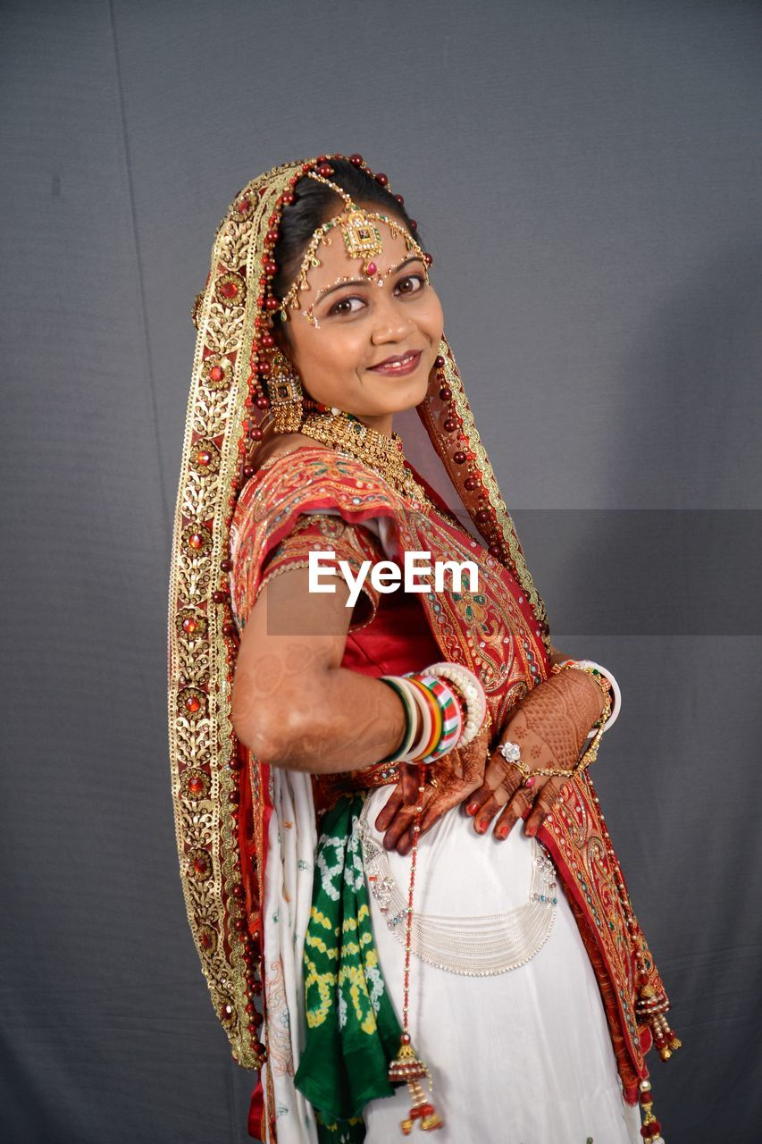 traditional clothing, clothing, indoors, women, smiling, one person, adult, beautiful woman, sari, young women, front view, lifestyles, event, newlywed, real people, looking at camera, bride, wedding ceremony, scarf