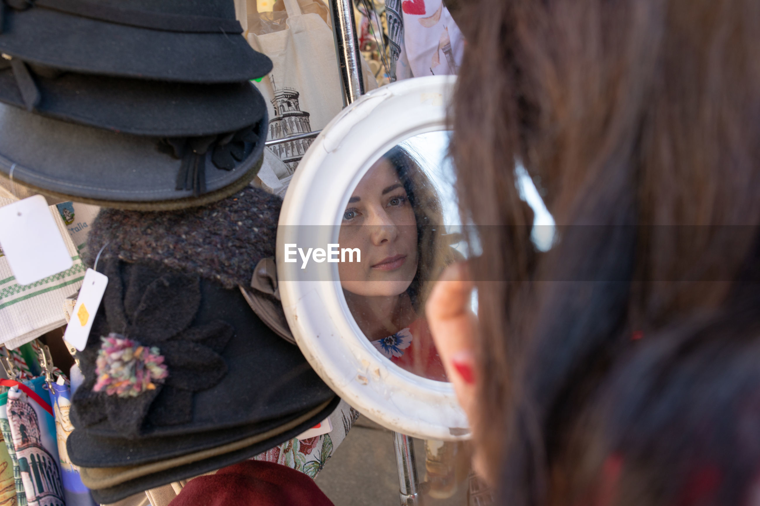Close-up of woman looking at mirror with reflection at market