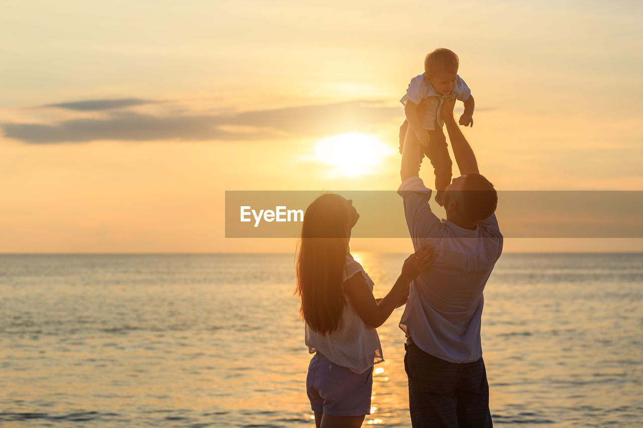 Father lifting son while standing with woman by sea during sunset