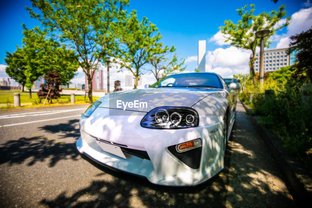 transportation, car, mode of transportation, motor vehicle, tree, land vehicle, plant, day, sunlight, nature, no people, focus on foreground, road, outdoors, city, sky, blue, shadow, architecture, close-up, luxury, silver colored