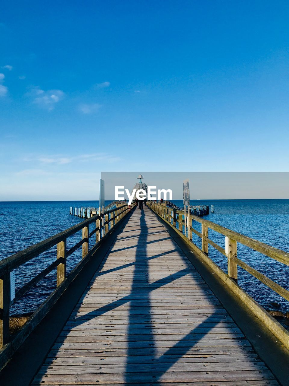 sea, water, sky, horizon over water, horizon, blue, scenics - nature, pier, nature, the way forward, direction, beauty in nature, railing, sunlight, day, wood - material, diminishing perspective, tranquility, tranquil scene, no people, outdoors, long