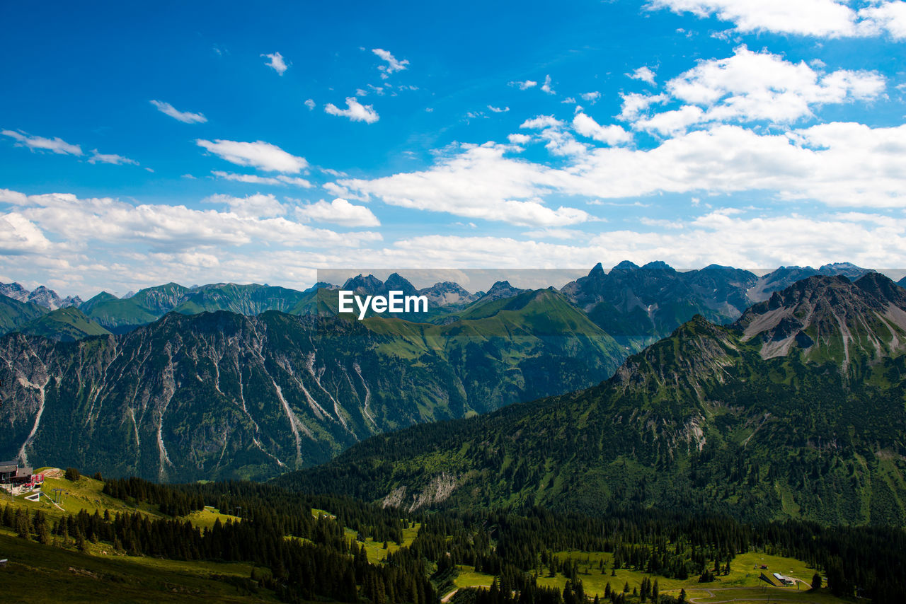 Scenic View Of Rocky Mountains Against Cloudy Sky