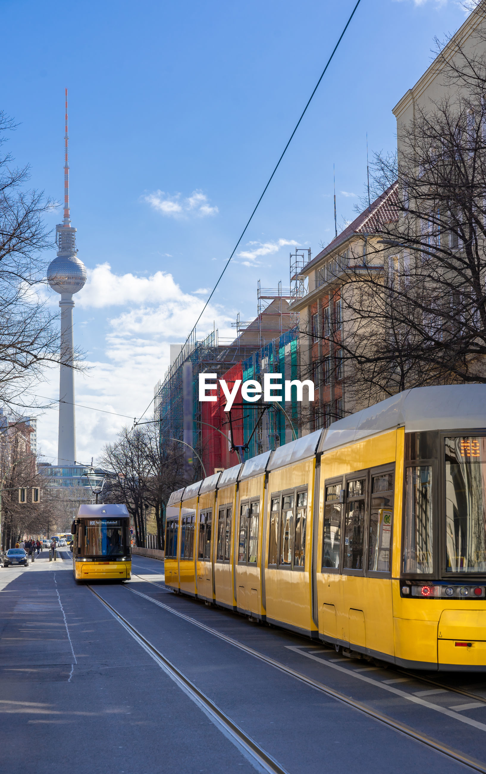 Tram on street amidst buildings in city against sky