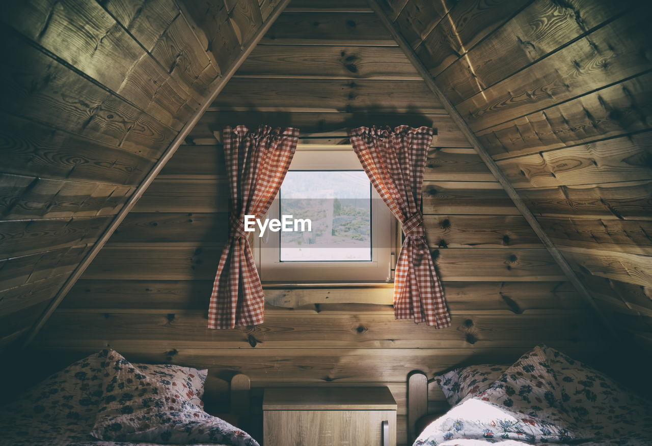 Small window in the roof of the wooden house with red curtains