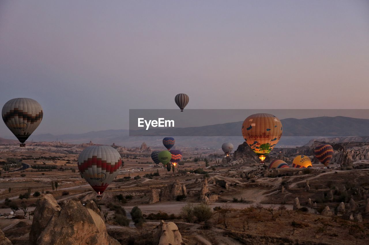HOT AIR BALLOONS FLYING OVER ROCK FORMATION AGAINST SKY