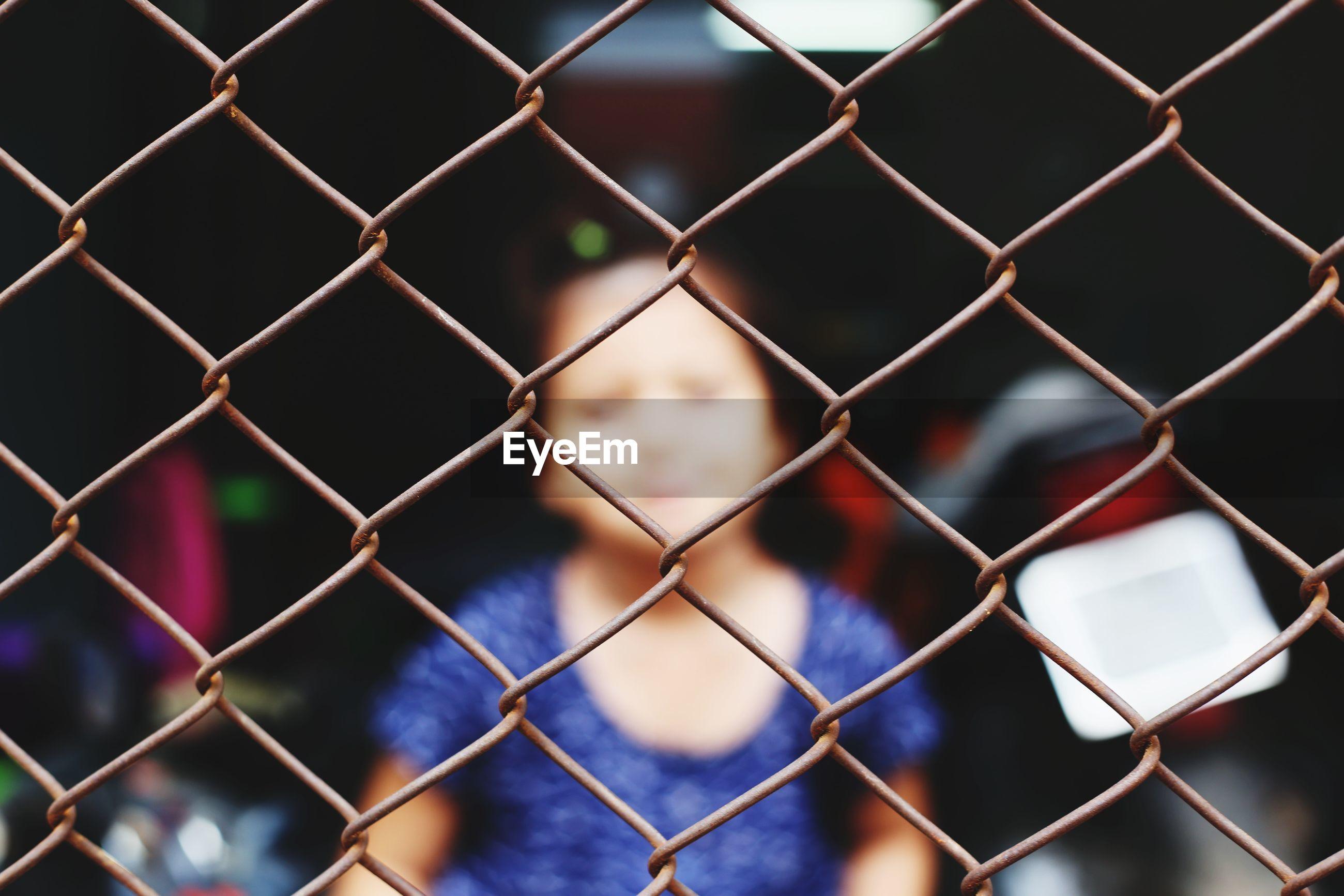 Girl seen through chainlink fence