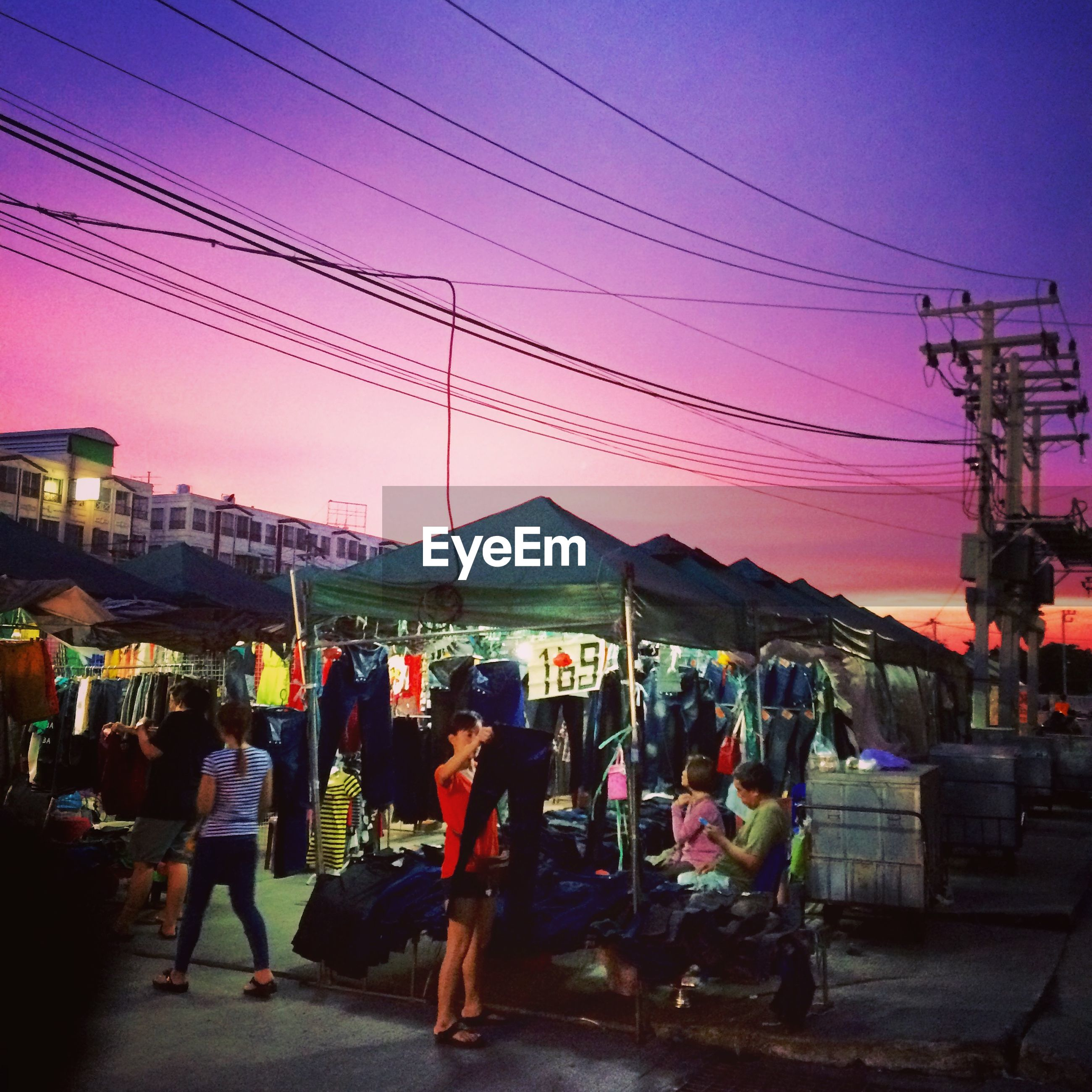 People shopping at market stall during sunset