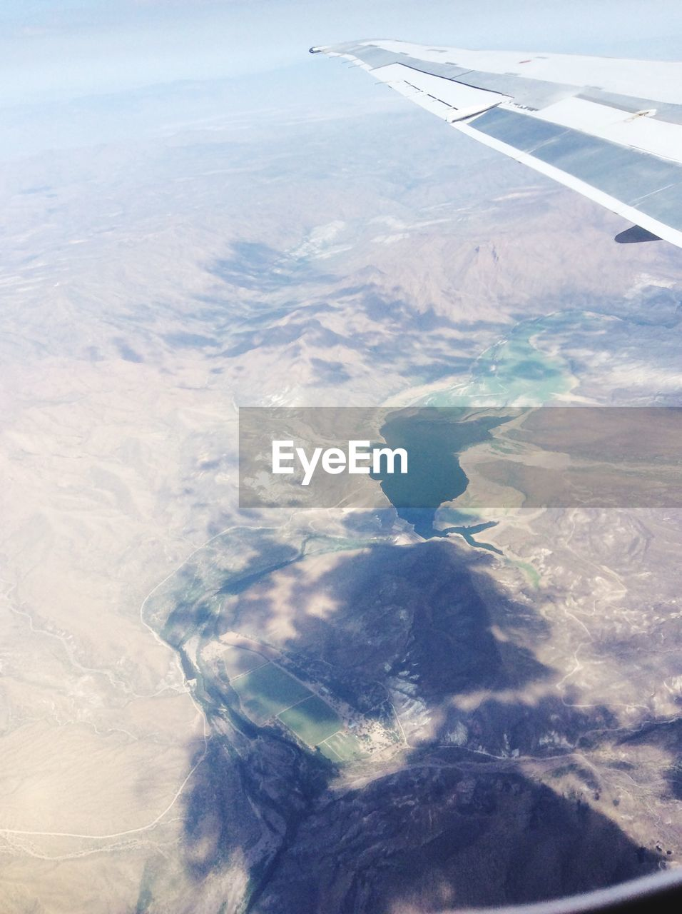 aerial view, airplane, airplane wing, nature, transportation, landscape, journey, scenics, flying, beauty in nature, mid-air, travel, aircraft wing, air vehicle, no people, vehicle part, mode of transport, day, outdoors, sea, view into land, sky, water, mountain, the natural world