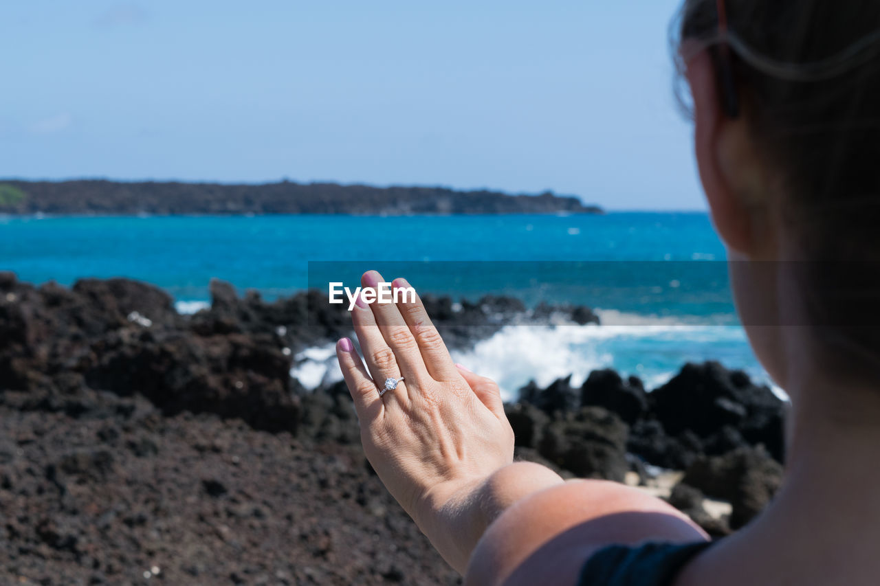 Close-up of hand of a woman on seashore