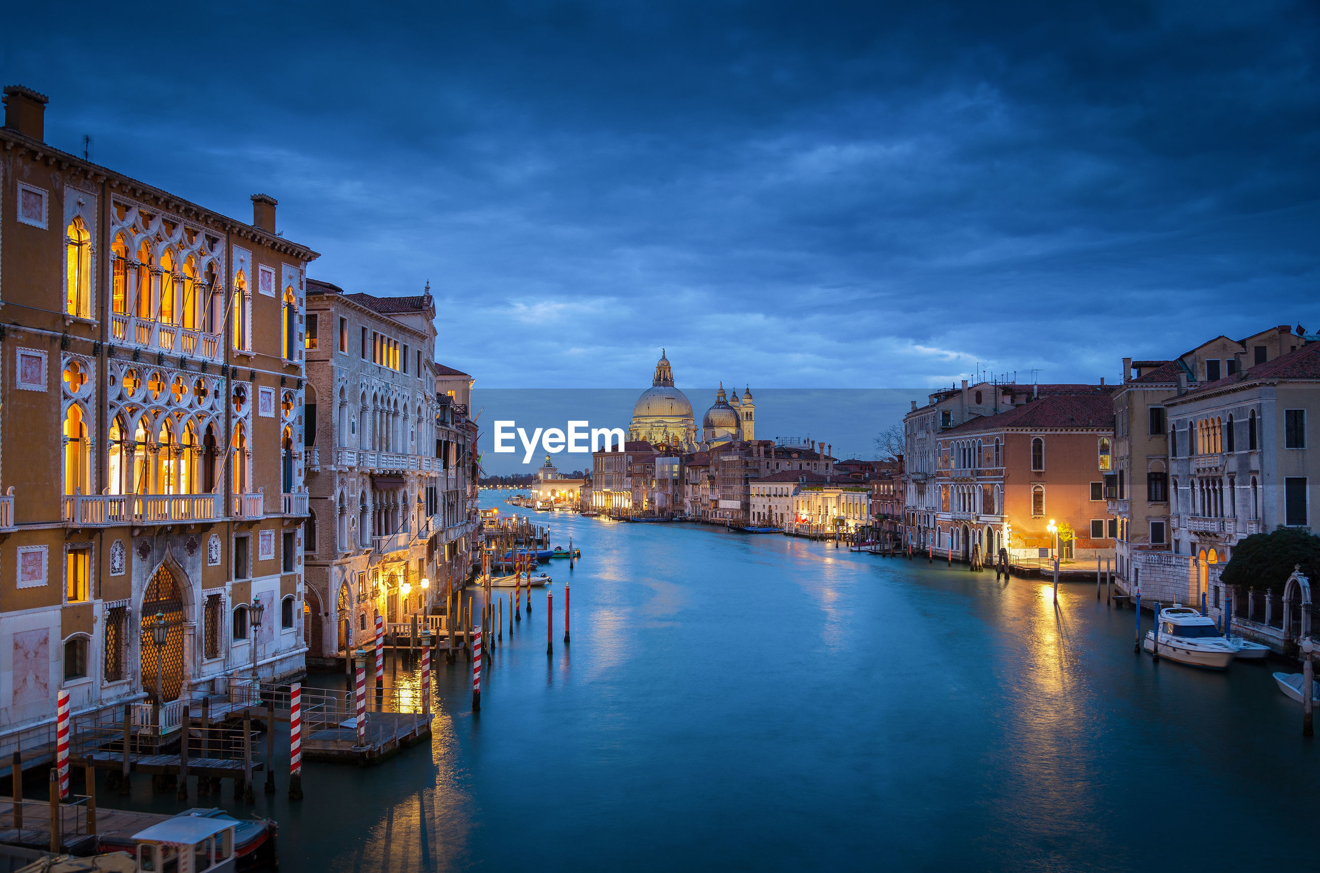 Grand canal amidst illuminated buildings in city at dusk