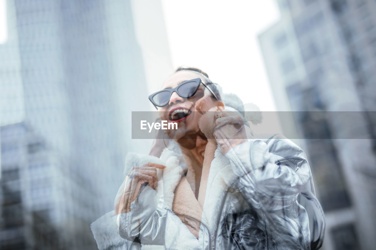 glasses, lifestyles, real people, architecture, adult, building exterior, one person, day, city, leisure activity, sunglasses, front view, looking, women, looking away, young adult, fashion, built structure, outdoors, office building exterior, beautiful woman, warm clothing