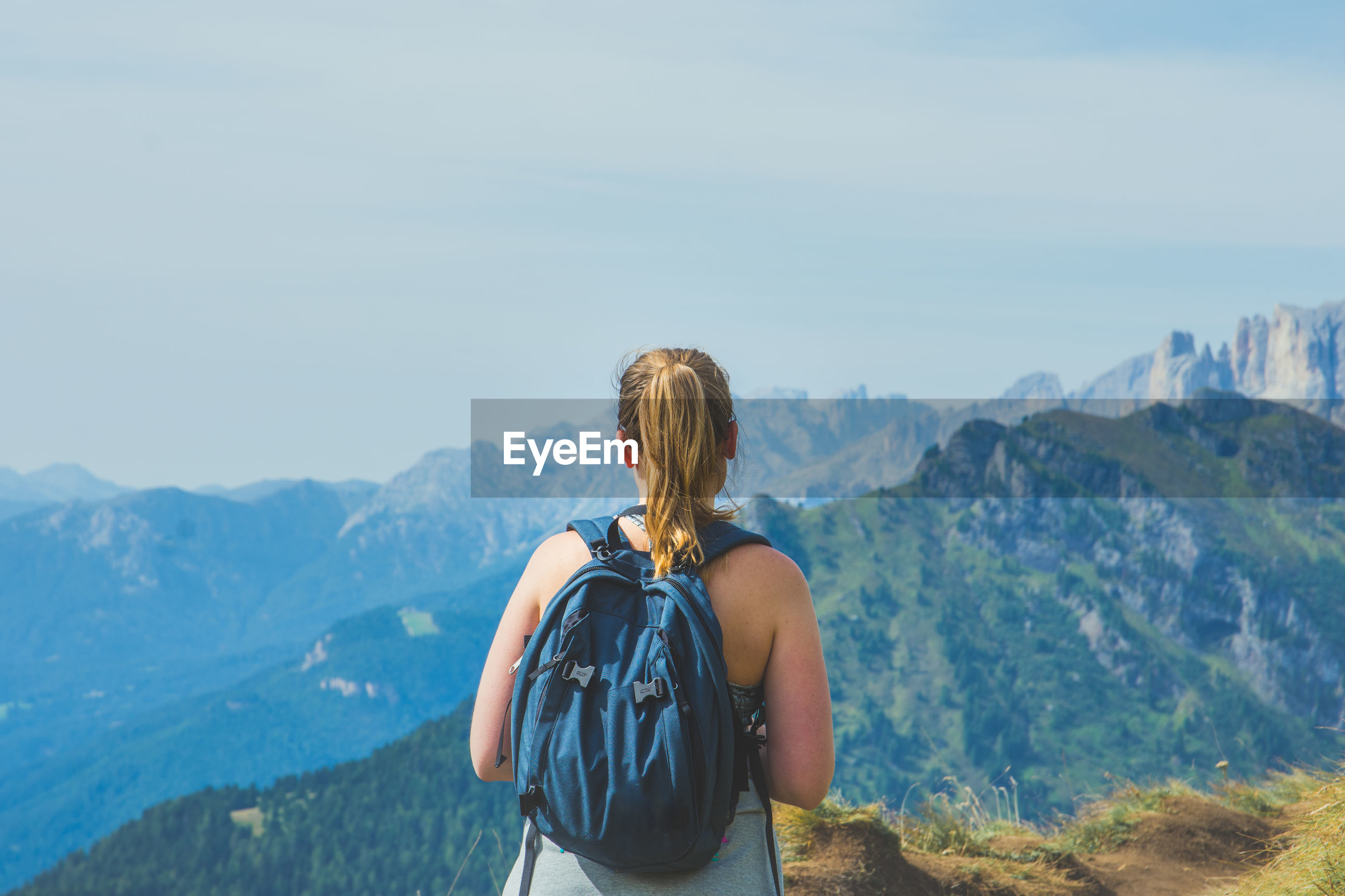 Rear view of backpacker standing on mountain against sky