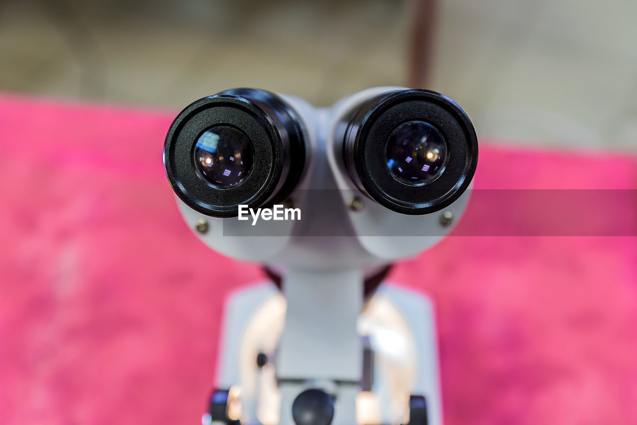 CLOSE-UP OF CAMERA AND EYEGLASSES ON METAL OUTDOORS