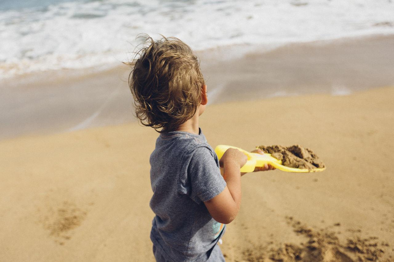 BOY HOLDING UMBRELLA ON BEACH