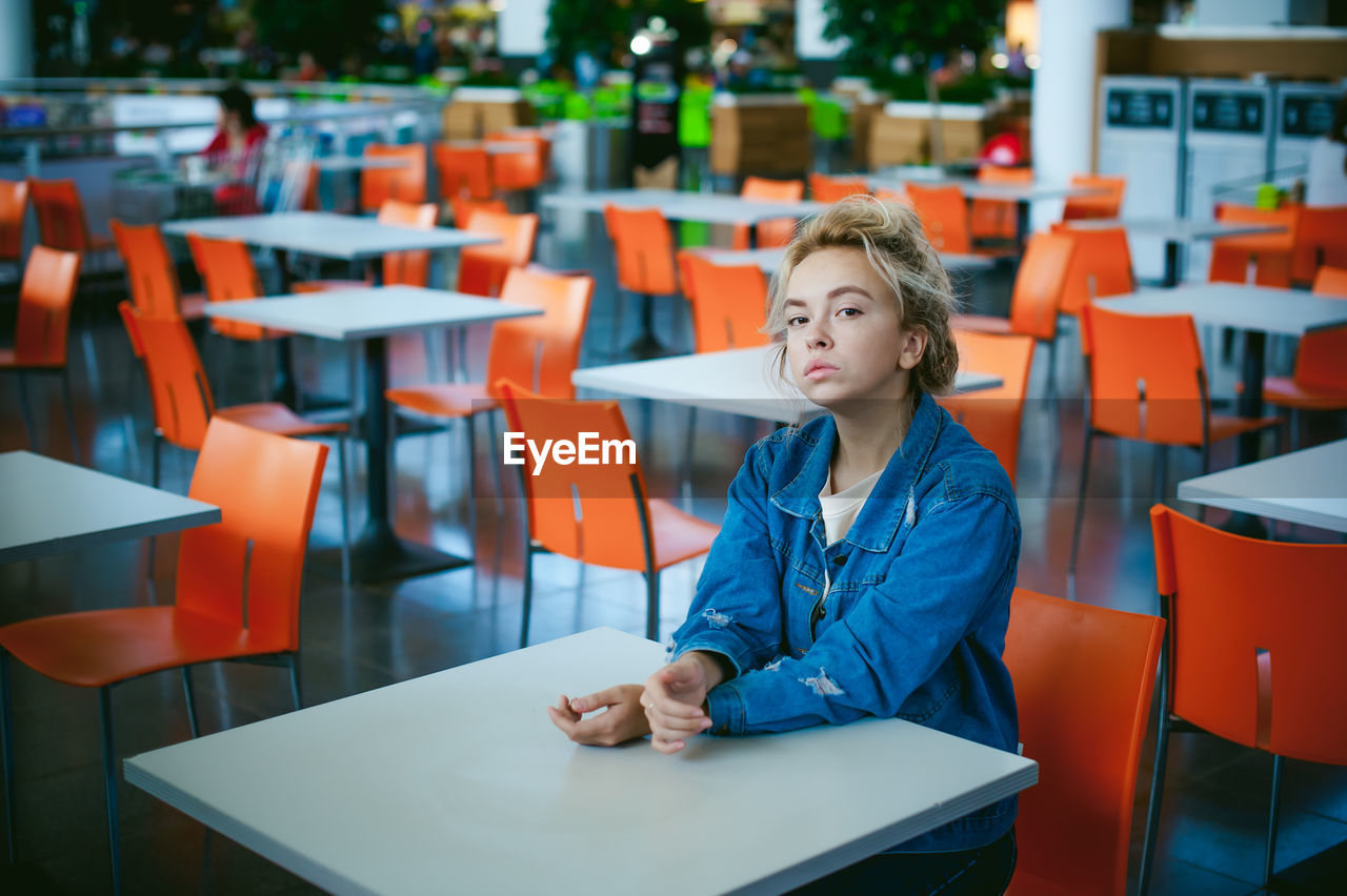Portrait Of Woman Sitting On Chair At Supermarket
