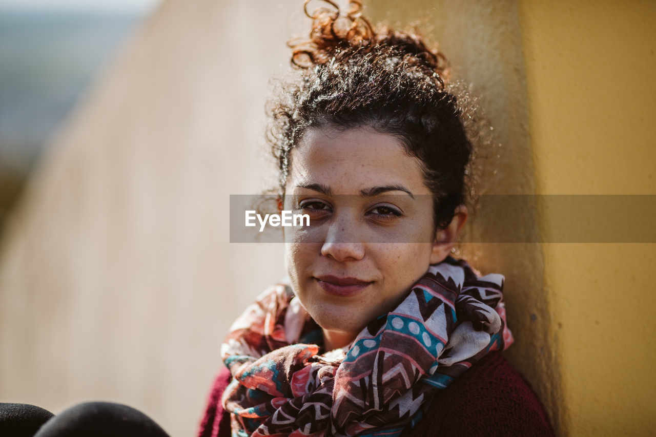 portrait, headshot, looking at camera, real people, lifestyles, one person, young adult, leisure activity, front view, women, smiling, young women, day, focus on foreground, adult, scarf, females, clothing, outdoors, hairstyle, warm clothing, beautiful woman