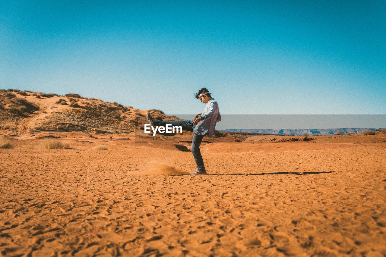 Side view of man kicking sand in desert