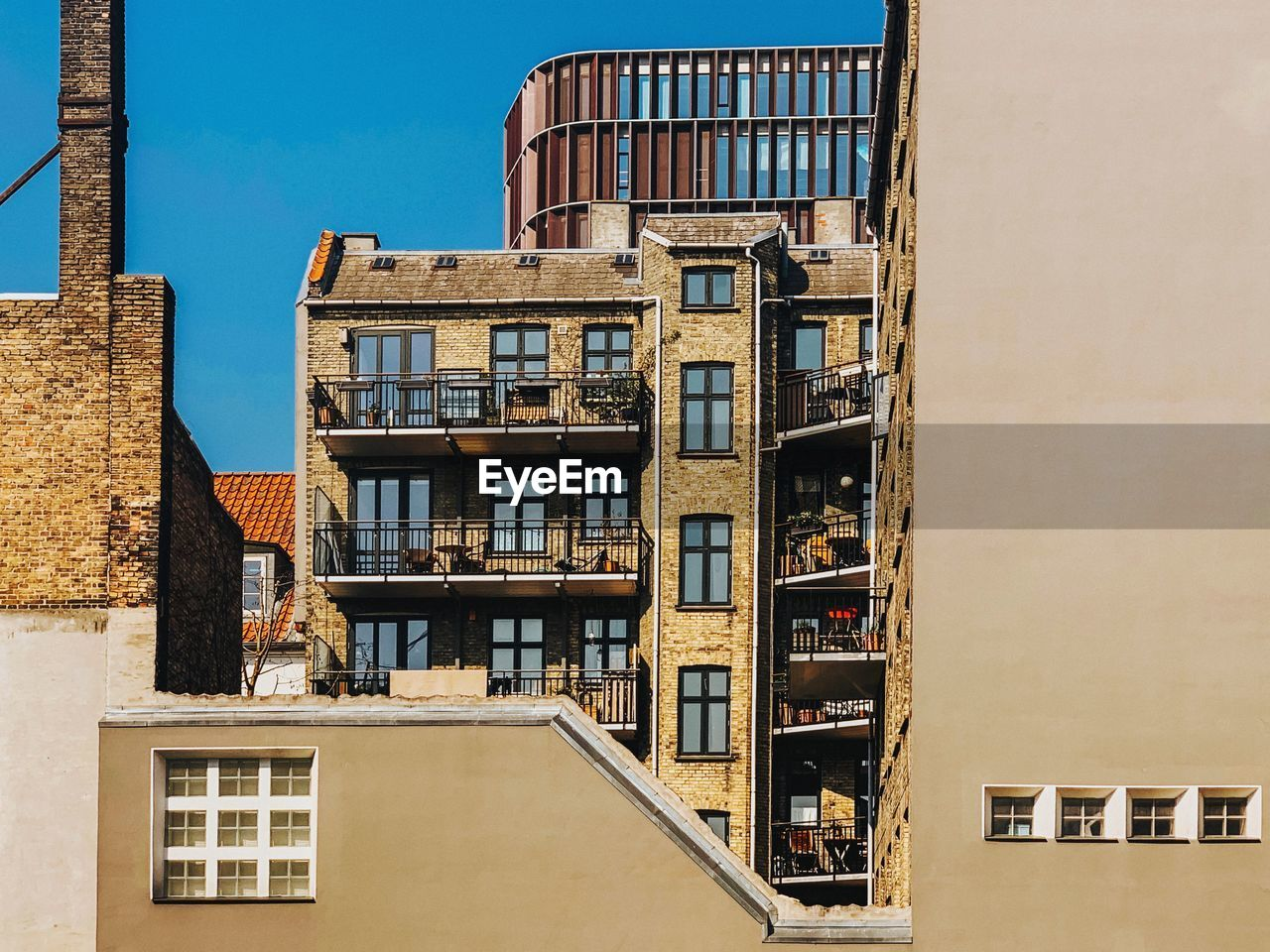 building exterior, built structure, architecture, building, window, residential district, sky, city, day, no people, nature, clear sky, sunlight, low angle view, outdoors, balcony, fire escape, apartment, wall, industry