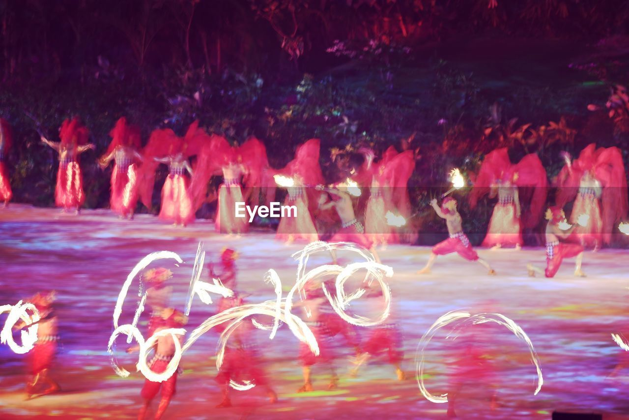 illuminated, motion, long exposure, water, night, pink color, glowing, nature, group of people, outdoors, red, light - natural phenomenon, real people, blurred motion, transparent, large group of people, sea